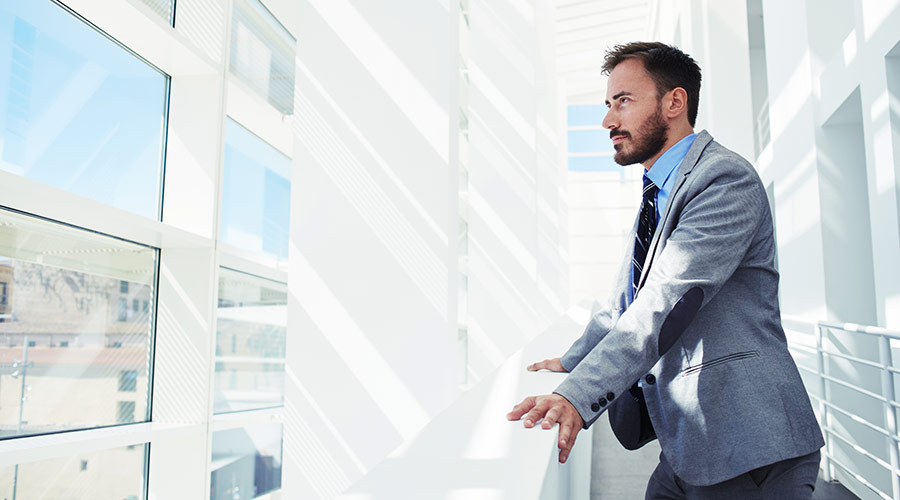 Young businessman gazing through window