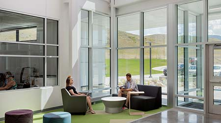 Two people sitting in an interior lobby