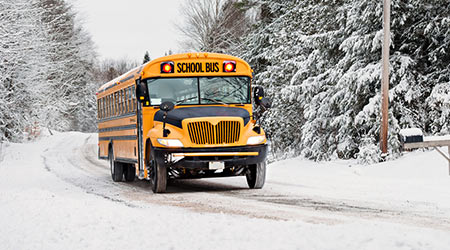 school bus driving on snow-covered road