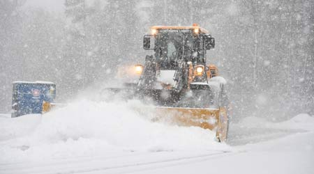 A snow plow clears the high school parking lot on town election day.