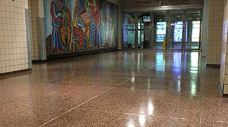 Shiny terrazo floor with mural in background at Penn Station