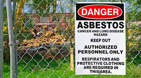 Asbestos warning posted on fence
