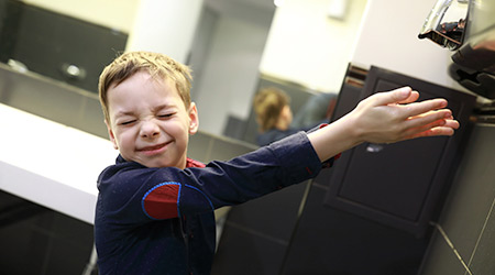 Young boy grimacing as he extends his hands toward a hot air hand dryer.