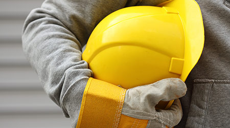 Man holding yellow helmet with safety gloves