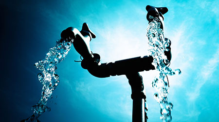 Double-spigot outdoor faucet with flowing water against a blue sky.