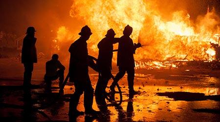 Silhouette of Firemen fighting a fire