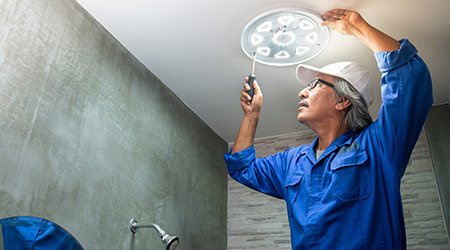 Electrician installs LED replacement lamp
