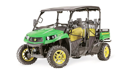 Three quarters photo of a green and yellow John Deere utility vehicle with seating for four.