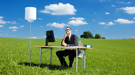 Smiling businessman working at a table in a green meadow with blue sky
