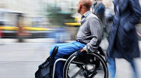 man using wheelchair on a city street