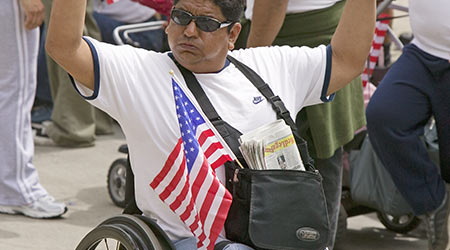 Man in wheelchair holds US flag