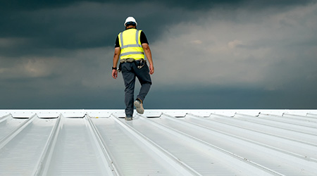Construction engineer wears safety uniform inspecting metal roofing