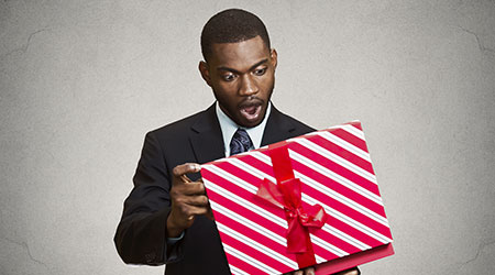 Young man in suit surprised at contents of candy-striped gift box.