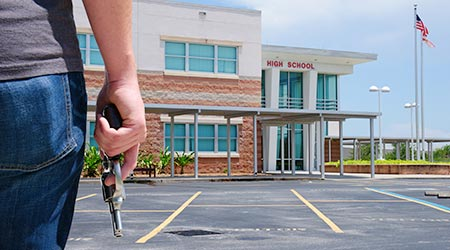Man with a gun standing in front of a high school