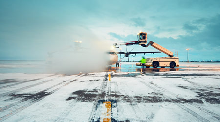 Airplane being de-iced, shown in a cloud of antifreeze.