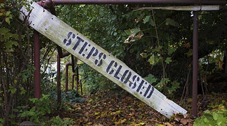 Steps Closed Sign in Front of Overgrown Outdoor Stairwell