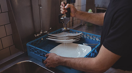 washing plates at sink in commercial kitchen