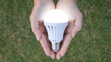 LED Bulb with lighting on hand with nature background