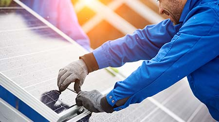 technician in blue suit installing photovoltaic blue solar modules with screw
