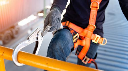 Construction worker uses safety harness and safety line at elevated height.