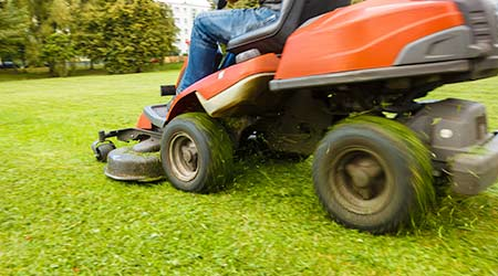 Gardner on ride-on lawn mower cutting grass.