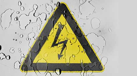 Electric shock sign covered with water drops