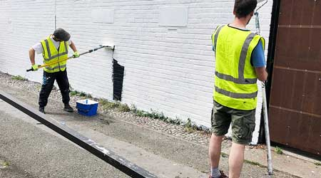 Two men in reflective vests painting a brick building white