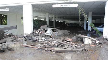 Post-flood debris pushed into hotel parking garage.