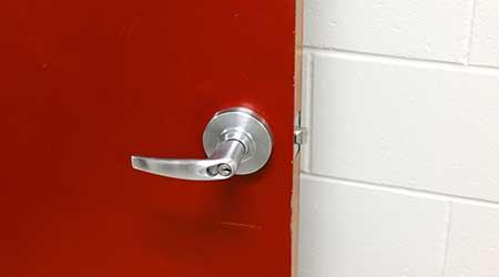 Close up door handle on red steel door.
