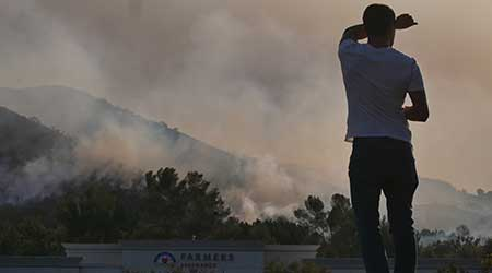 Smoke over building in Woolsey Wildfire in California, person shielding face.