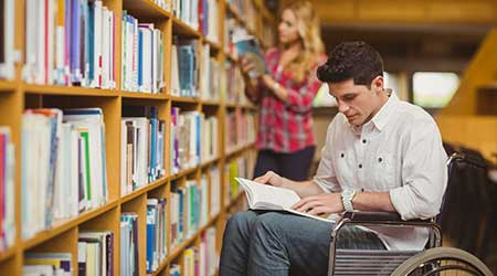 Student in wheelchair talking with classmate in library