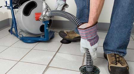 Technician using drain cleaning equipment