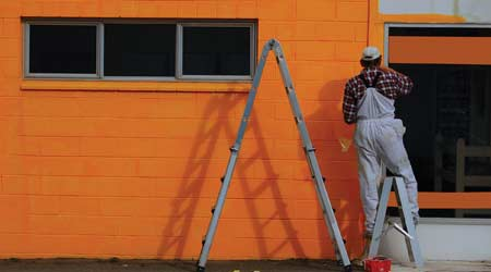 Man painting building orange