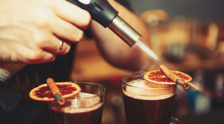 Bartender burns cinnamon sticks for mulled wine with gas torch in bar.