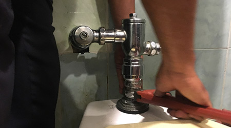 Plumber repairing flushing toilet with wrench