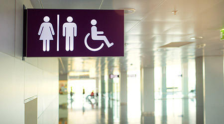 Airport public restroom signs with a disabled access symbol