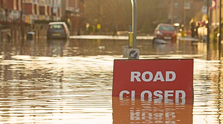 A 'Road Closed' sign partially covered in flood water
