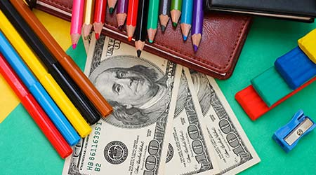 Pens, colored pencils, book, hundred dollar bills