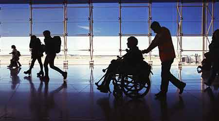 Silhouette of man in wheelchair and people carrying luggage in airport