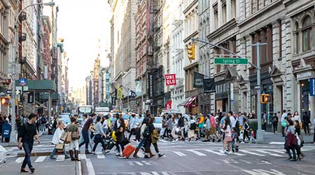 Busy crowds of people walk across the intersection of Broadway and Spring Street in the SoHo neighborhood of Manhattan, NYC