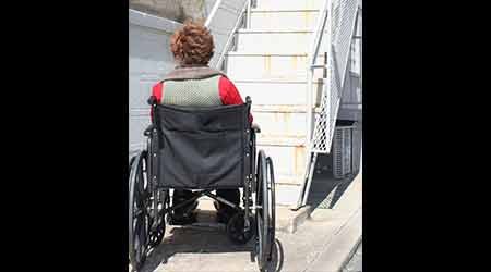 Wheelchair-using person at bottom of stairs