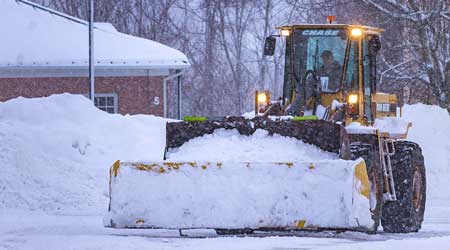 Snow removal equipment clears snow from a parking lot