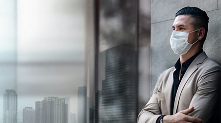 Man in medical mask looking over buildings.
