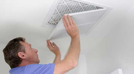 Technician closing ceiling grill after replacing an air filter