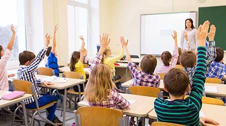 school kids with teacher sitting in classroom