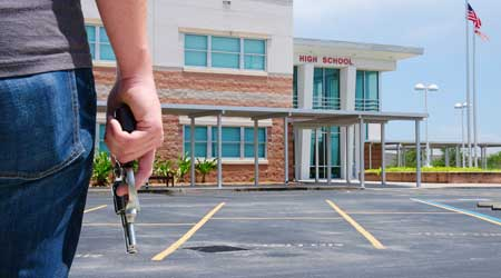A man with a gun in front of a school