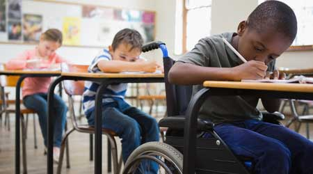 Student using wheelchair in classroom