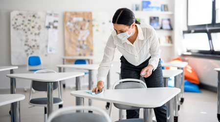 Worker cleaning classroom