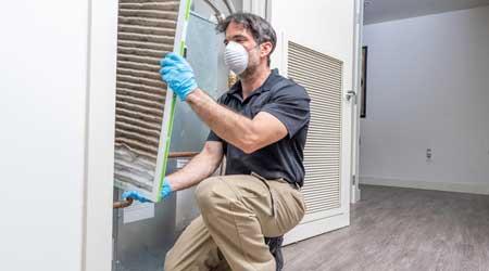 HVAC technician removing a dirty air filter from a heat pump