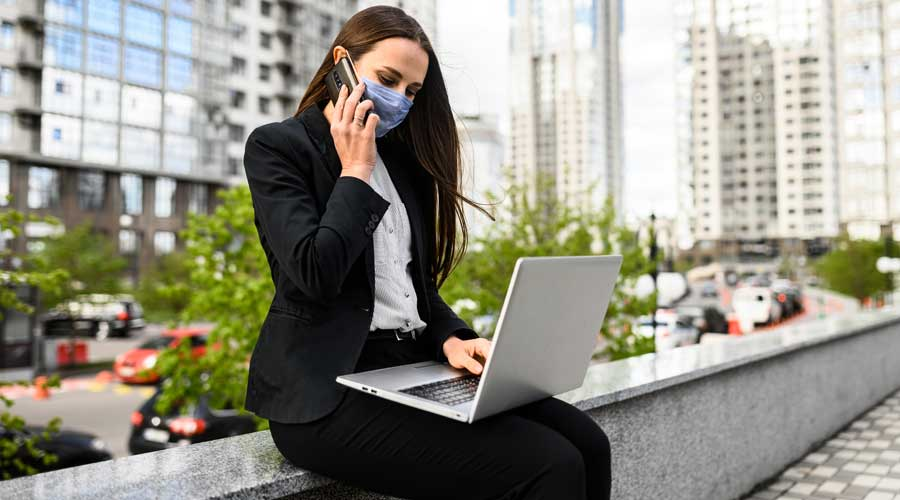 A young woman in protective medical mask working with laptop outdoors